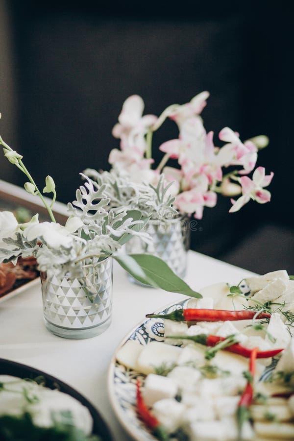 Elegancki kwiecisty wystrój na ślubu stole Biali eustoma, orchidei kwiaty w zakąskach na ślubnym centerpiece i zdjęcia stock