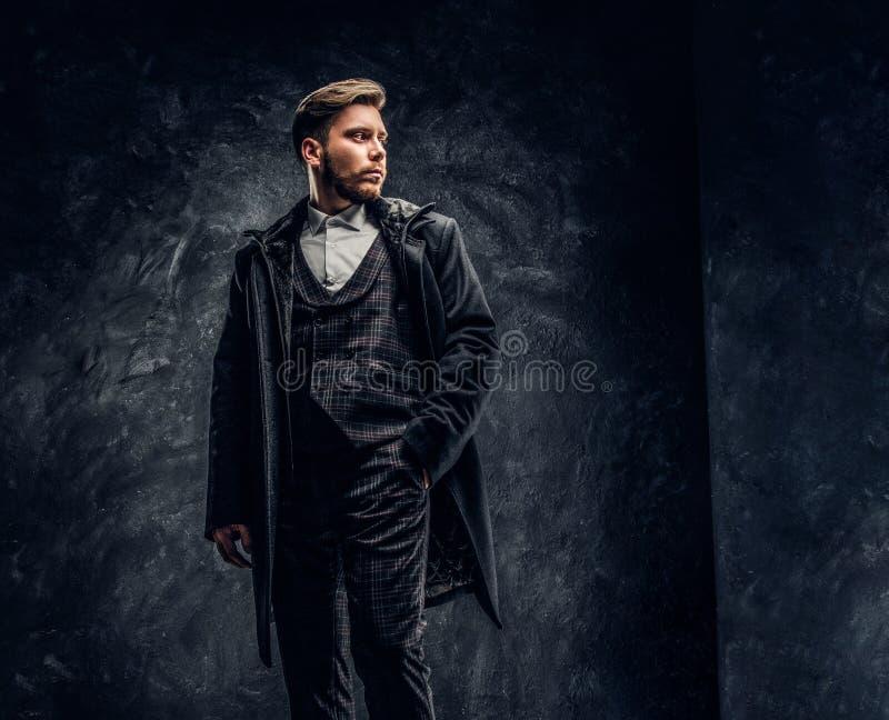 Elegancki mężczyzna ubierał w eleganckim kostiumu i żakiet pozuje przeciw zmrokowi z ręką w kieszeni textured ścianę fotografia royalty free