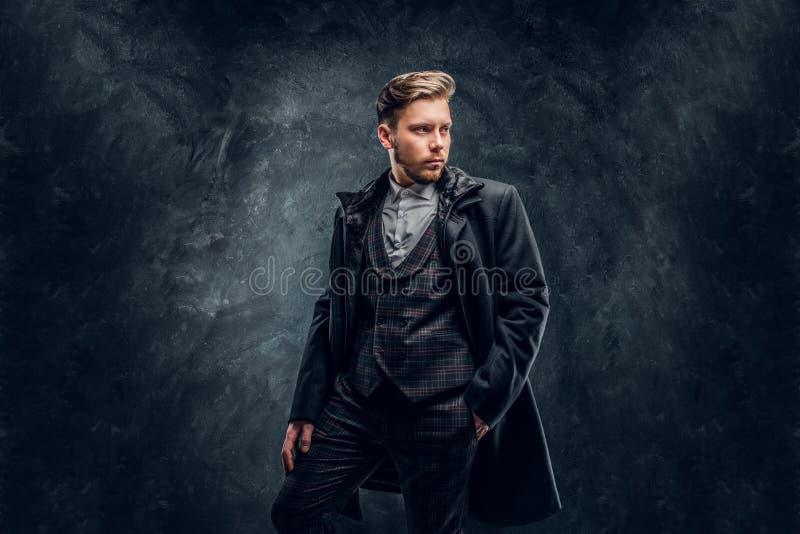 Elegancki mężczyzna ubierał w eleganckim kostiumu i żakiet pozuje przeciw zmrokowi z ręką w kieszeni textured ścianę obrazy stock