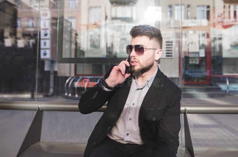 Elegancki mężczyzna w kostiumu mówi telefonem na transport publiczny przerw ławce zdjęcie royalty free