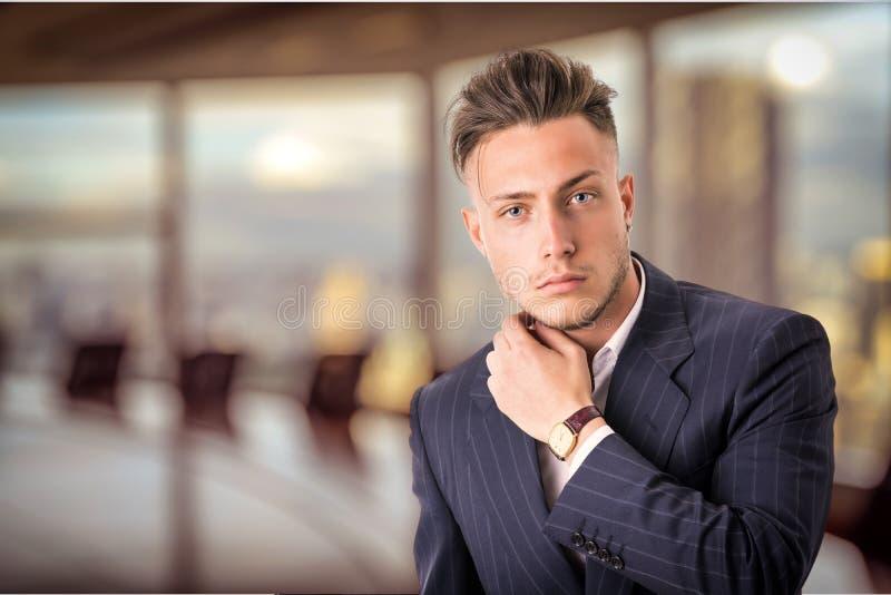 Elegancki młody człowiek z garniturem w biurze zdjęcie royalty free