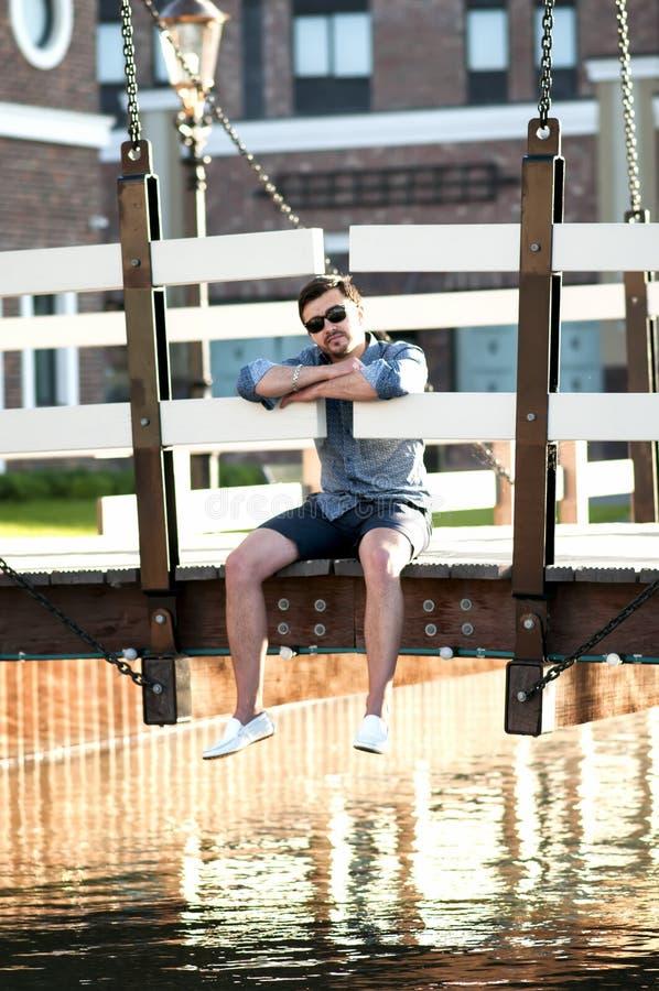 Elegancki mężczyzna obsiadanie na drewnianym moscie fotografia royalty free