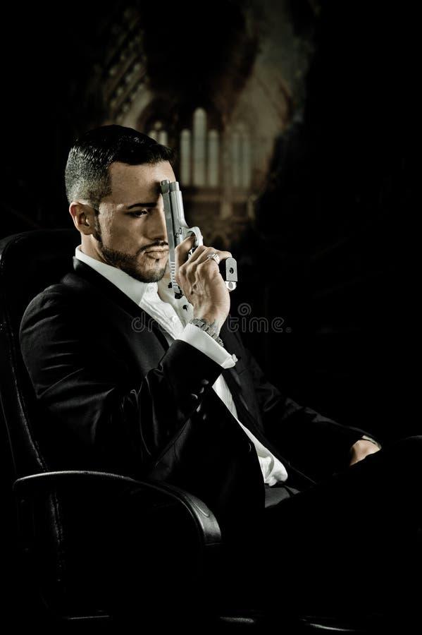 Elegancki mężczyzna obsiadanie w krzesła mienia pistolecie zdjęcia royalty free