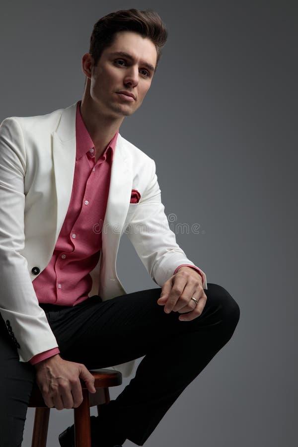 Elegancki mężczyzna odpoczywa jego rękę na nodze podczas gdy patrzejący daleko od zdjęcie royalty free