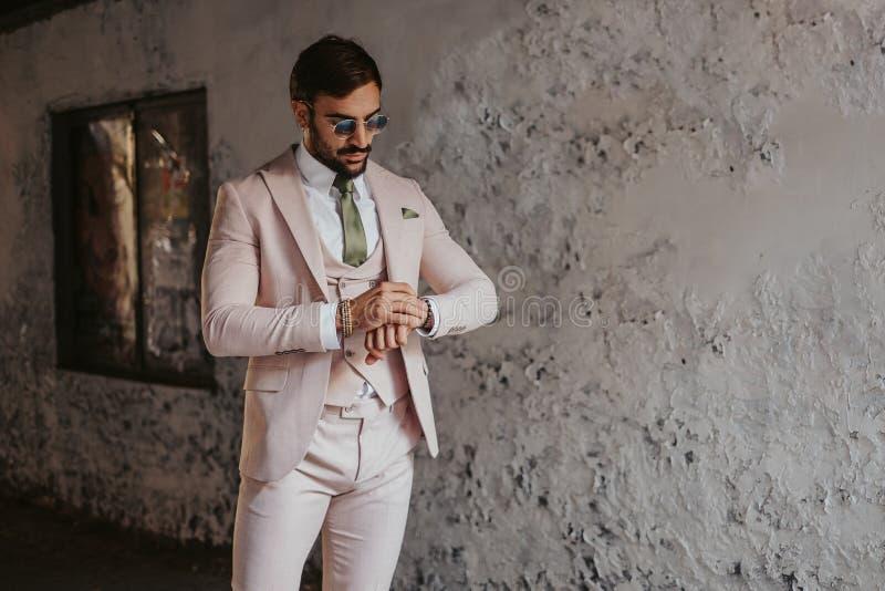 Elegancki mężczyzna patrzeje jego zegarek w budynku korytarzu obrazy royalty free