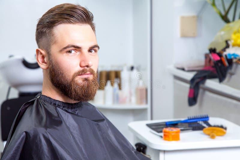 Elegancki mężczyzna patrzeje kamerę w fryzjera męskiego sklepie zdjęcie stock
