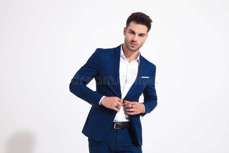 Elegancki mężczyzna patrzeje kamera i przystosowywa jego kurtkę zdjęcie royalty free