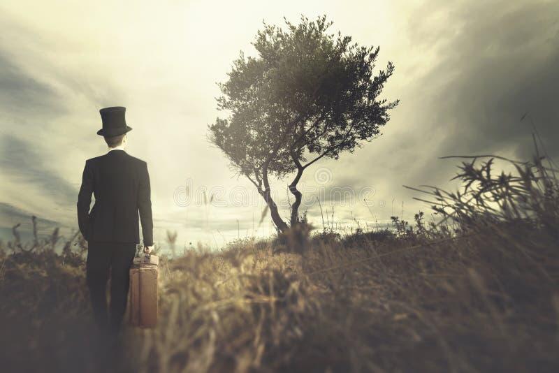 Elegancki mężczyzna podróżuje w surrealistycznym miejscu z jego walizką obraz royalty free