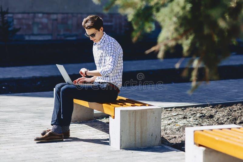 elegancki mężczyzna pracuje na laptopie przy ulicą zdjęcie royalty free