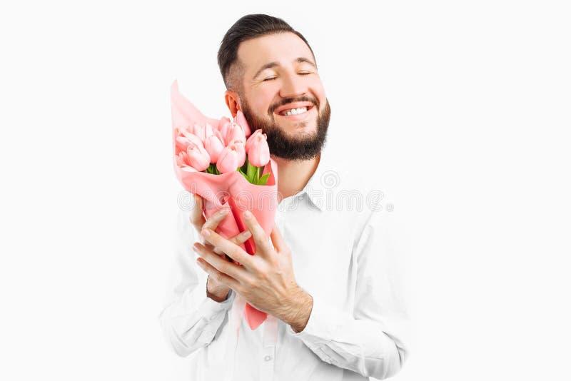 Elegancki mężczyzna trzyma bukiet tulipany z brodą, prezent dla walentynka dnia zdjęcie stock