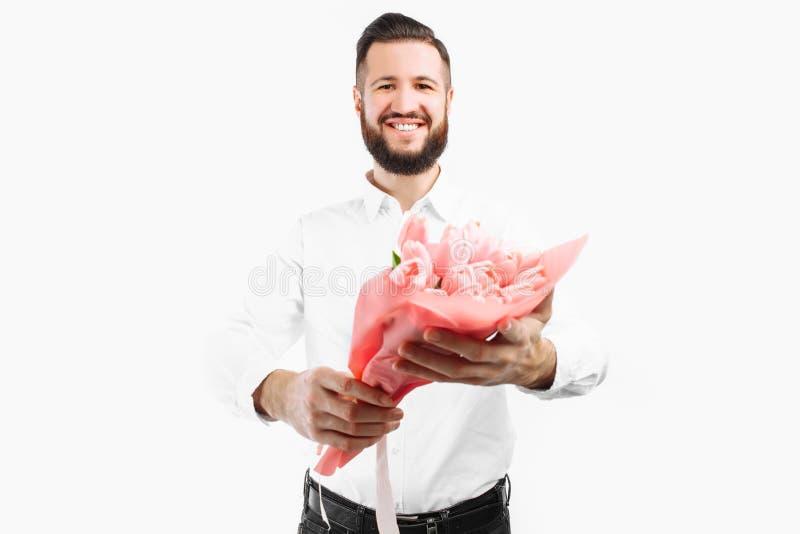 Elegancki mężczyzna trzyma bukiet tulipany z brodą, prezent dla walentynka dnia obraz stock