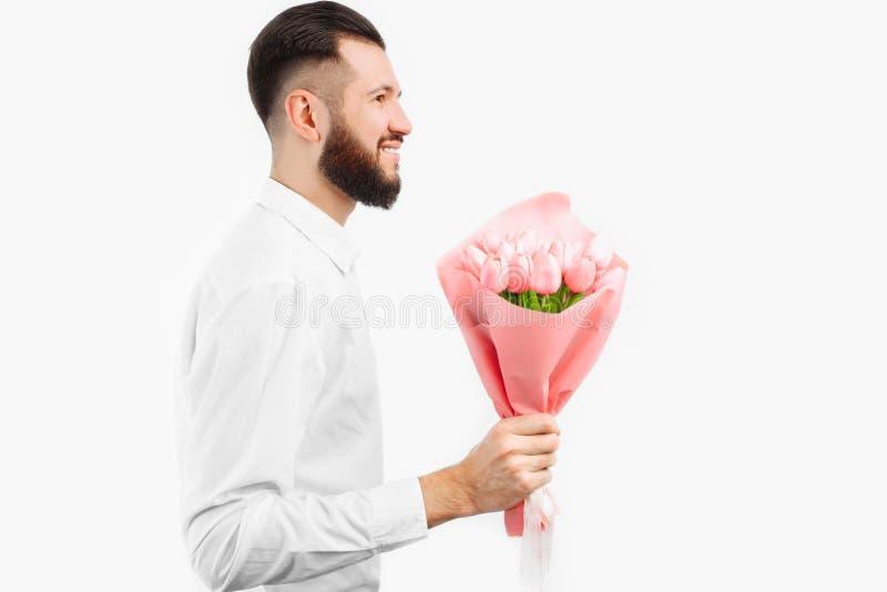 Elegancki mężczyzna trzyma bukiet tulipany z brodą, prezent dla walentynka dnia fotografia stock