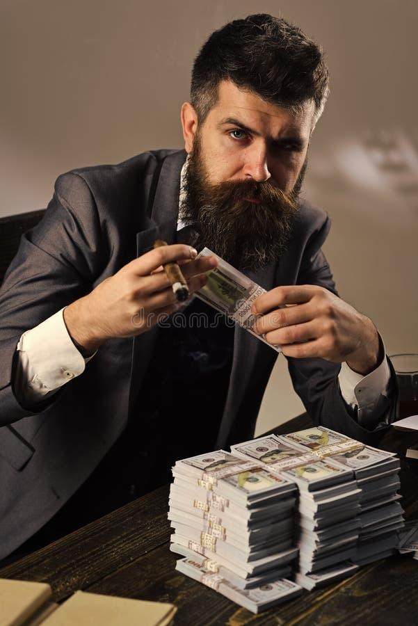 Elegancki mężczyzna w kostiumu Obsługuje obsiadanie przy stołem z stosami pieniądze, liczy zysk Bezprawny gotówkowy pojęcie Bizne zdjęcie royalty free