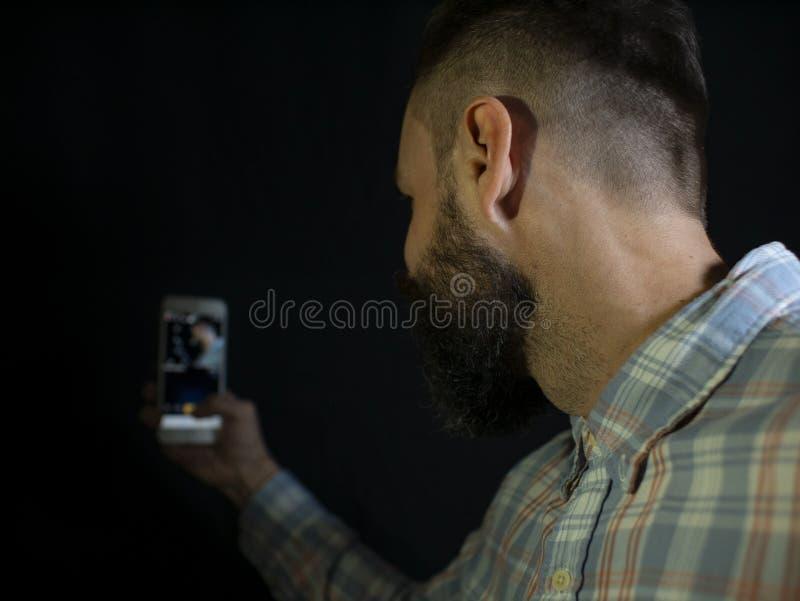 Elegancki mężczyzna z brodą i wąsów spojrzeniami w telefon i robi selfie na czarnym tle fotografia royalty free
