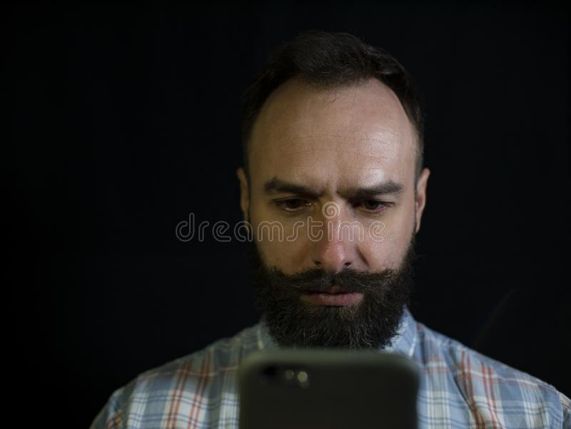 Elegancki mężczyzna z brodą i wąsy ostrożnie spojrzenia przy telefonem na czarnym tle obraz stock