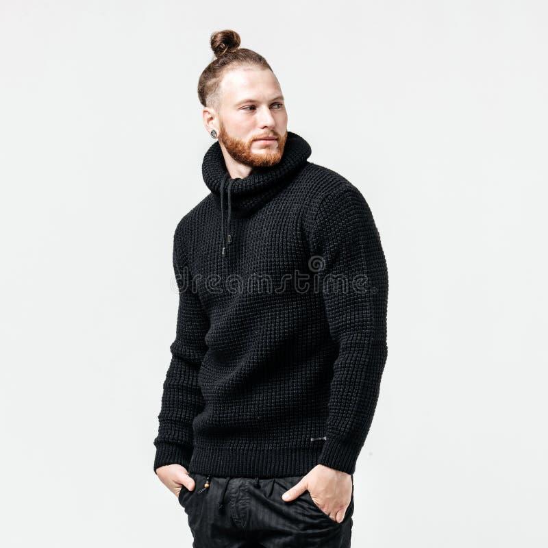 Elegancki mężczyzna z brody i babeczki fryzurą ubierał w czarnych trykotowych puloweru i spodń pozach w studiu na bielu obrazy stock