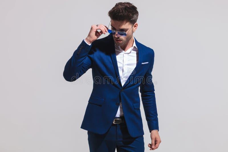 Elegancki mężczyzna zdejmuje jego okulary przeciwsłonecznych i spojrzenia zestrzelają obrazy stock