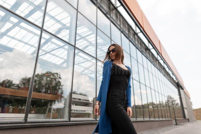 Elegancki młoda kobieta modniś w rocznika błękitnym trykotowym przylądku w eleganckich cajgach w koszulce z koronką w modnych oku zdjęcia stock