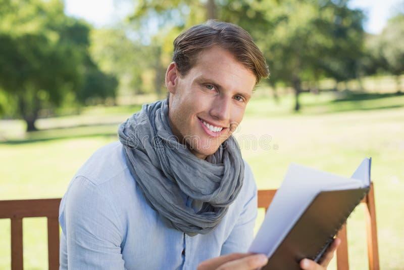 Elegancki młodego człowieka mienia czasopismo ono uśmiecha się przy kamerą zdjęcia stock