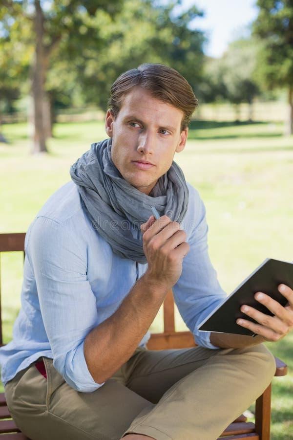 Elegancki młodego człowieka mienia notepad i główkowanie zdjęcia stock