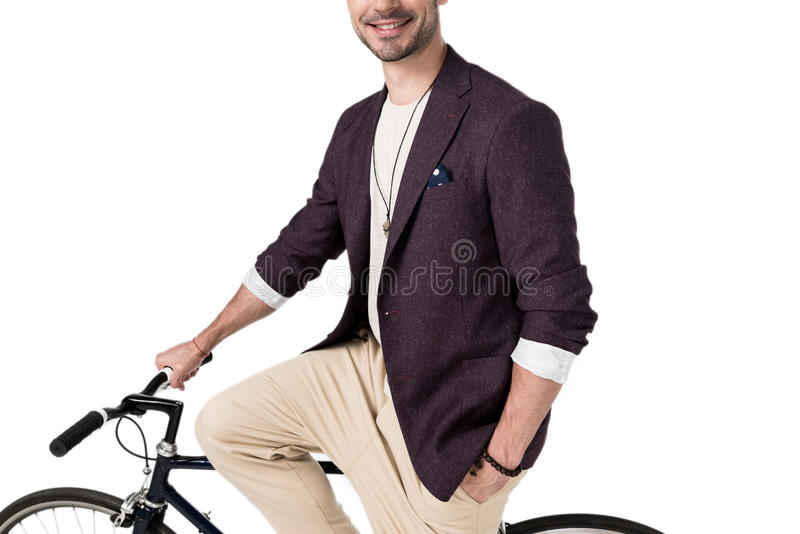Elegancki młodego człowieka obsiadanie na modnisia ono uśmiecha się i bicyklu obrazy stock