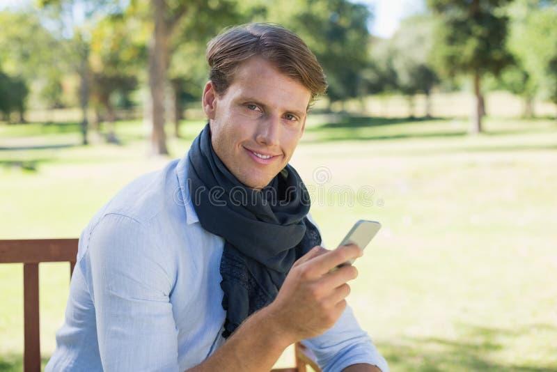 Elegancki młodego człowieka obsiadanie na parkowej ławce wysyła tekst zdjęcie stock