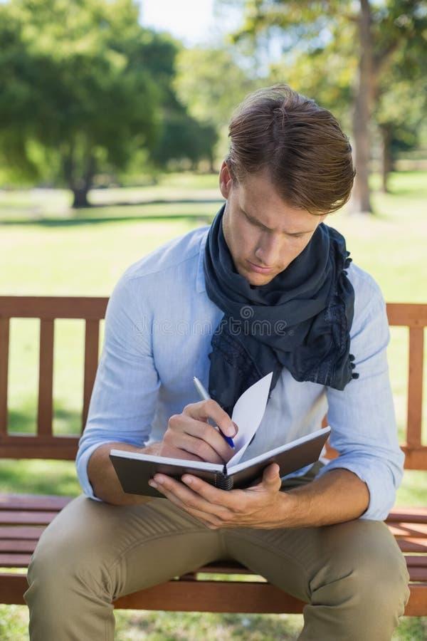 Elegancki młodego człowieka writing w jego notepad na parkowej ławce obraz stock