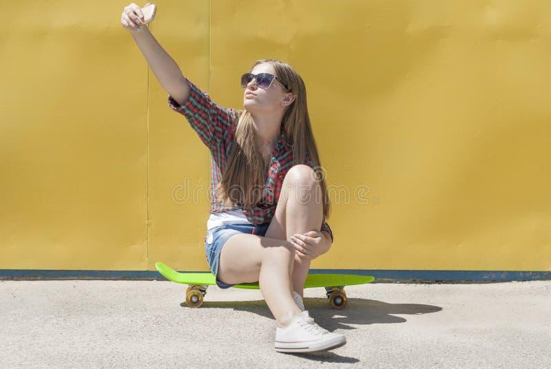 Elegancki młodej dziewczyny obsiadanie na deskorolka obraz royalty free