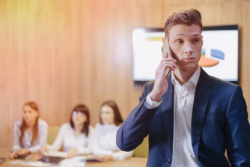 Elegancki młody biznesmen jest ubranym koszula na tle pracujący biuro z ludźmi opowiada na telefonie komórkowym i kurtkę fotografia royalty free