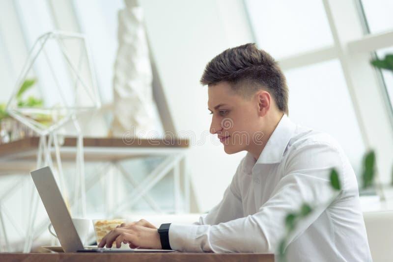 Elegancki młody biznesmen patrzeje laptop z uśmiechem podczas gdy pracujący na projekcie w wygodnej małej kawiarni fotografia royalty free