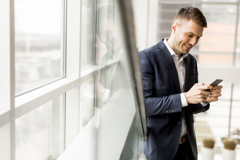 Elegancki młody biznesmen używa telefon komórkowego na schody w offic zdjęcie royalty free