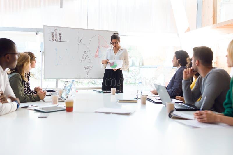 Elegancki młody bizneswoman wyjaśnia projekt na coworking miejscu jej koledzy zdjęcia stock
