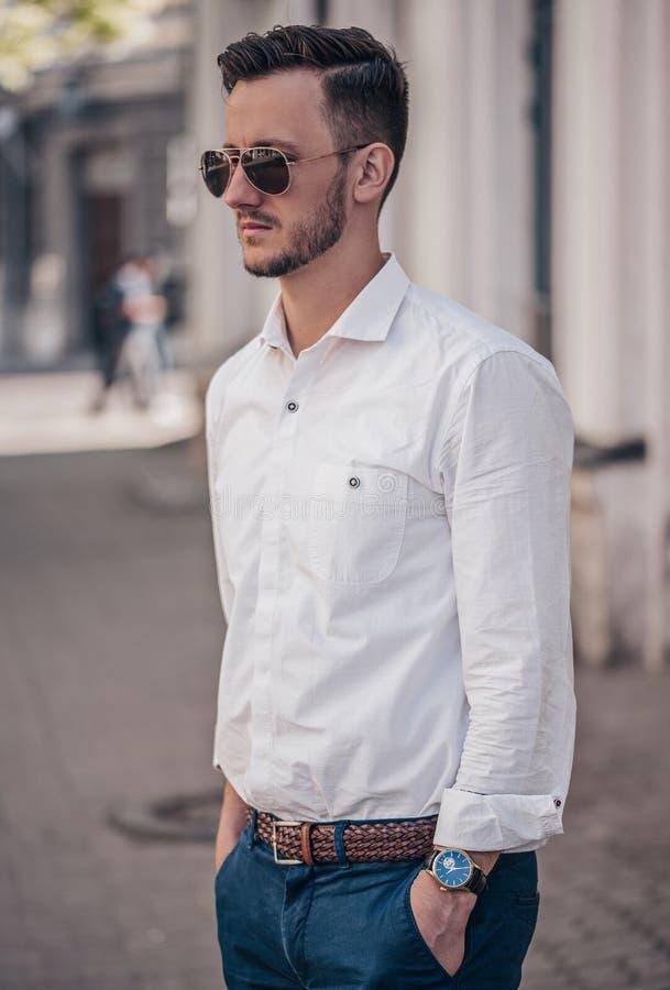Elegancki młody człowiek pozuje z zegarkiem w plenerowym obraz stock