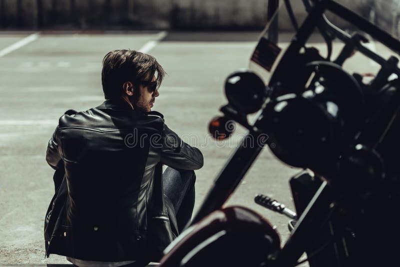 Elegancki młody człowiek siedzi blisko motocyklu i patrzeje daleko od w skórzanej kurtce zdjęcia royalty free