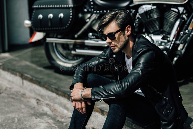 Elegancki młody człowiek siedzi na betonowym krawężniku blisko motocyklu w skórzanej kurtce i okularach przeciwsłonecznych fotografia stock