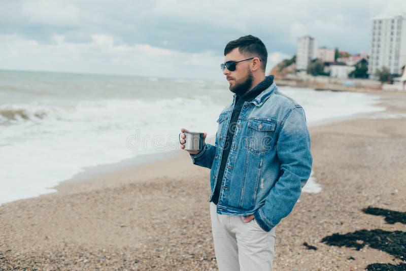 Elegancki młody człowiek stoi blisko oceanu z filiżanką herbata z brodą fotografia royalty free
