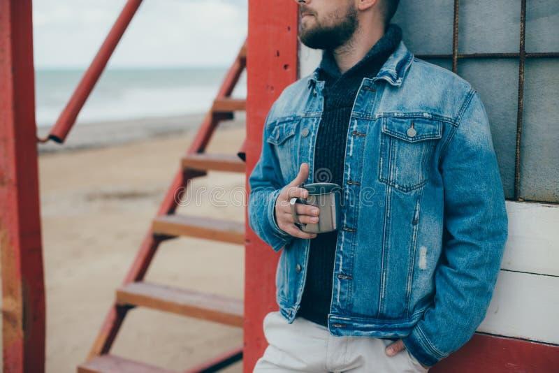 Elegancki młody człowiek stoi blisko oceanu z filiżanką herbata z brodą obrazy stock