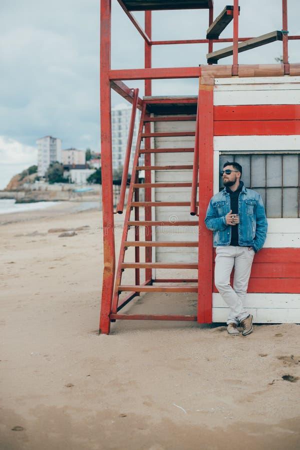 Elegancki młody człowiek stoi blisko oceanu z filiżanką herbata z brodą zdjęcia stock