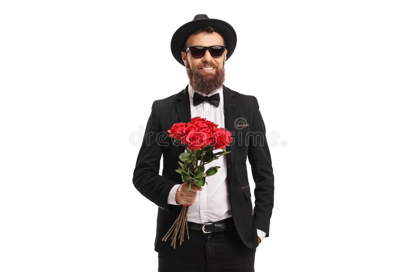 Elegancki młody człowiek trzyma wiązkę czerwone róże zdjęcie stock
