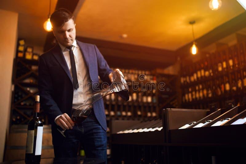 Elegancki młody człowiek w błękitnym kostiumu i białym koszulowym dolewania winie od dekantatoru obraz stock