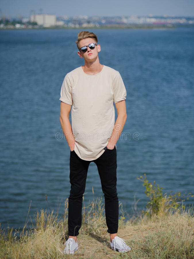 Elegancki młody człowiek w okularach przeciwsłonecznych Wysoki, chłodno faceta odprowadzenie blisko rzeki na zamazanym tle, Szkoł fotografia stock