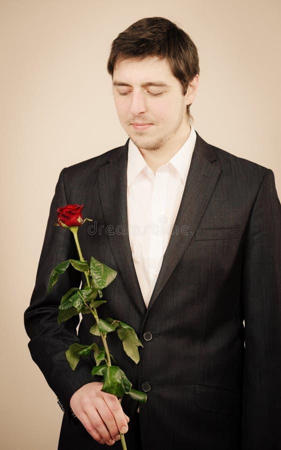 Elegancki młody człowiek z czerwieni różą obrazy royalty free