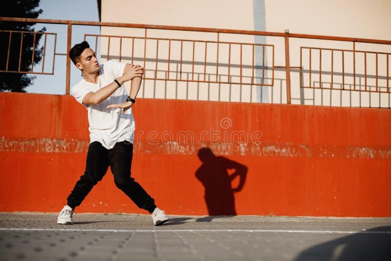 Elegancki młody facet ubierający w cajgach i białej koszulce jest dancingowym brakedance w ulicie przeciw malującej betonowej ści zdjęcie royalty free