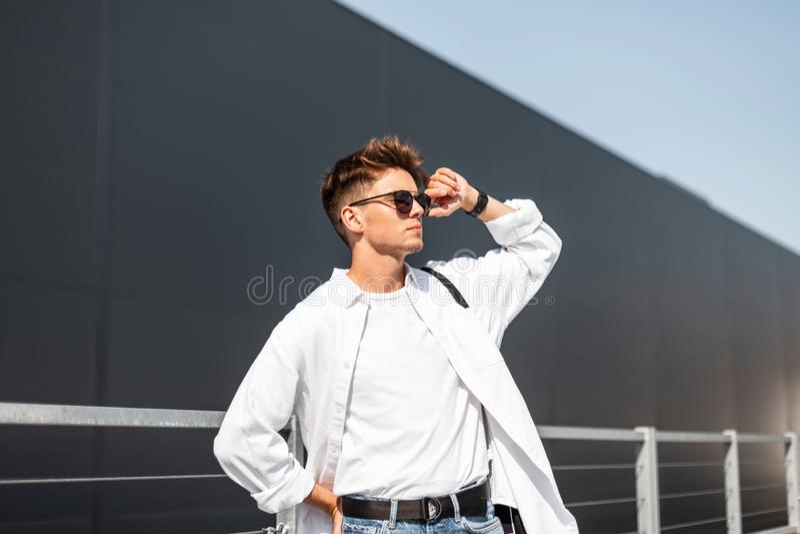 Elegancki młody modnisia mężczyzna prostuje modnych okulary przeciwsłonecznych Europejski faceta model w eleganckiej białej koszu obrazy stock
