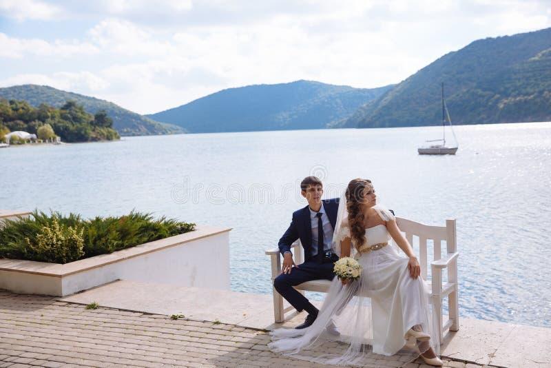 Elegancki młody państwo młodzi w białej sowicieckiej ślubnej sukni siedzi na ławce przed rzeką i wzgórzami zdjęcia royalty free