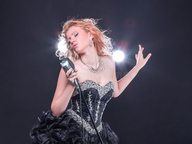 Elegancki młody piosenkarz wykonuje jazzową piosenkę z mikrofonem zdjęcia stock