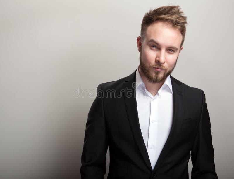 Elegancki młody przystojny brodaty mężczyzna w klasycznym czarnym kostiumu & białej koszula fotografia royalty free