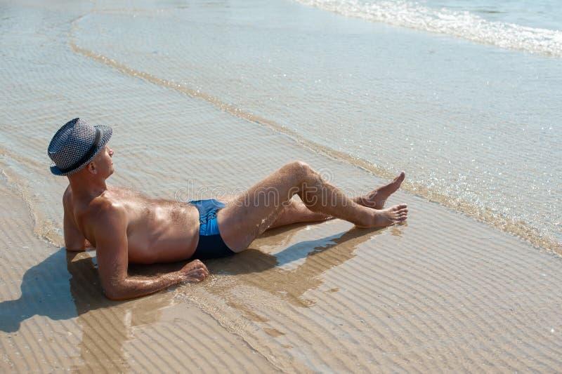 Elegancki młody samiec modela mężczyzny lying on the beach na plażowym piasku jest ubranym modnisia lata kapelusz cieszy się lato zdjęcia stock