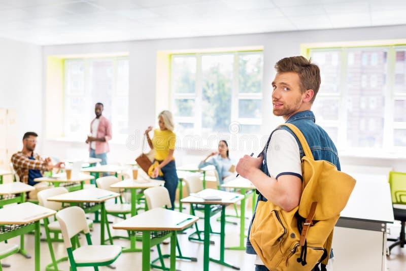 elegancki młody uczeń w sali lekcyjnej szkoła wyższa z zamazanymi kolegami z klasy zdjęcia stock