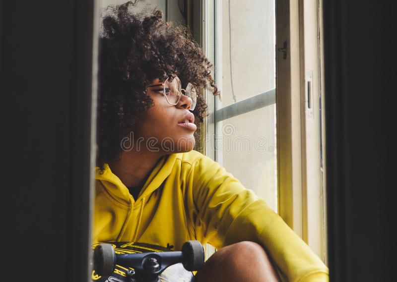 Elegancki młody zmysłowy czarny zadumany kobiety obsiadanie blisko okno z deskorolka zdjęcie stock